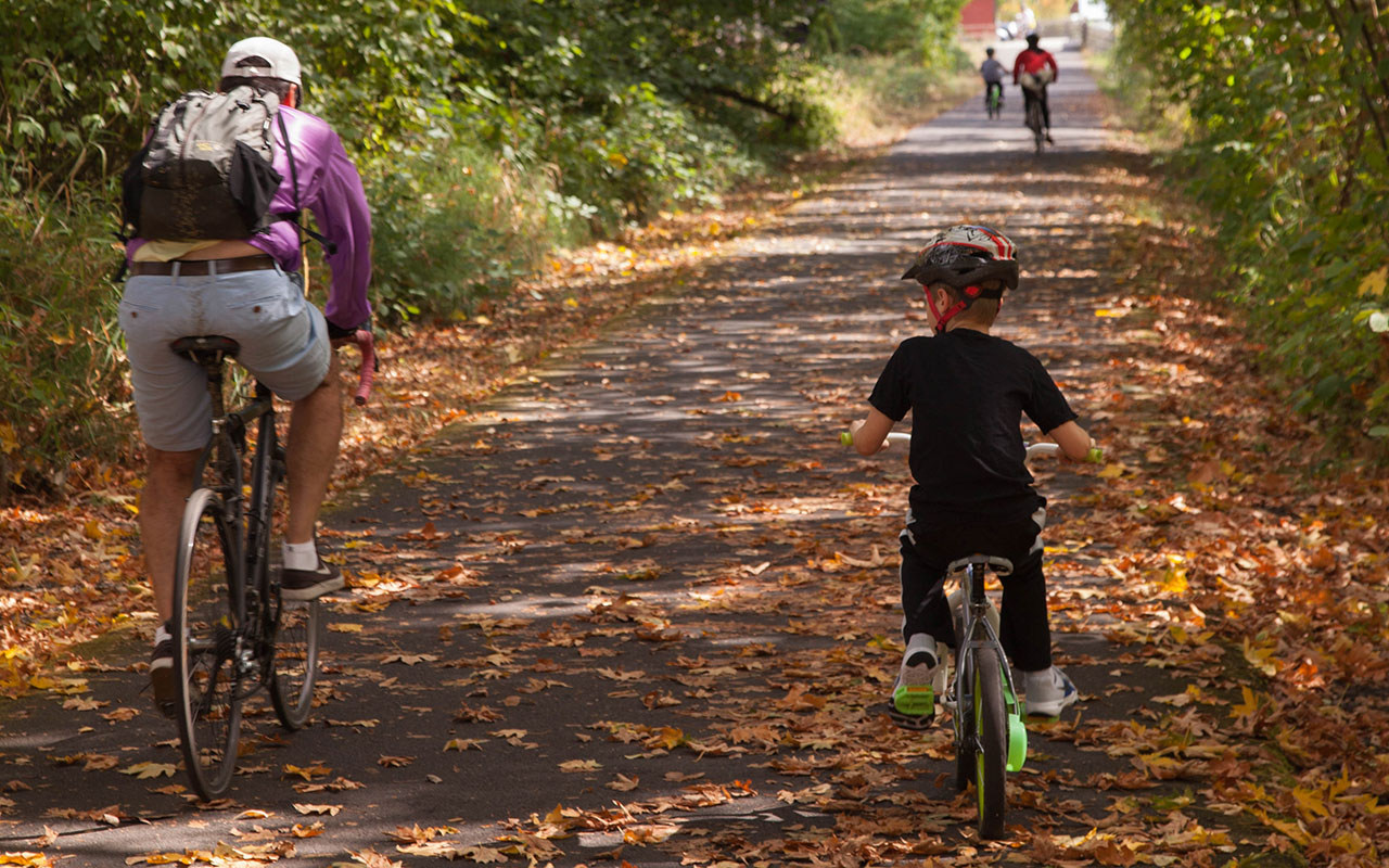 man and boy bicycling on a path