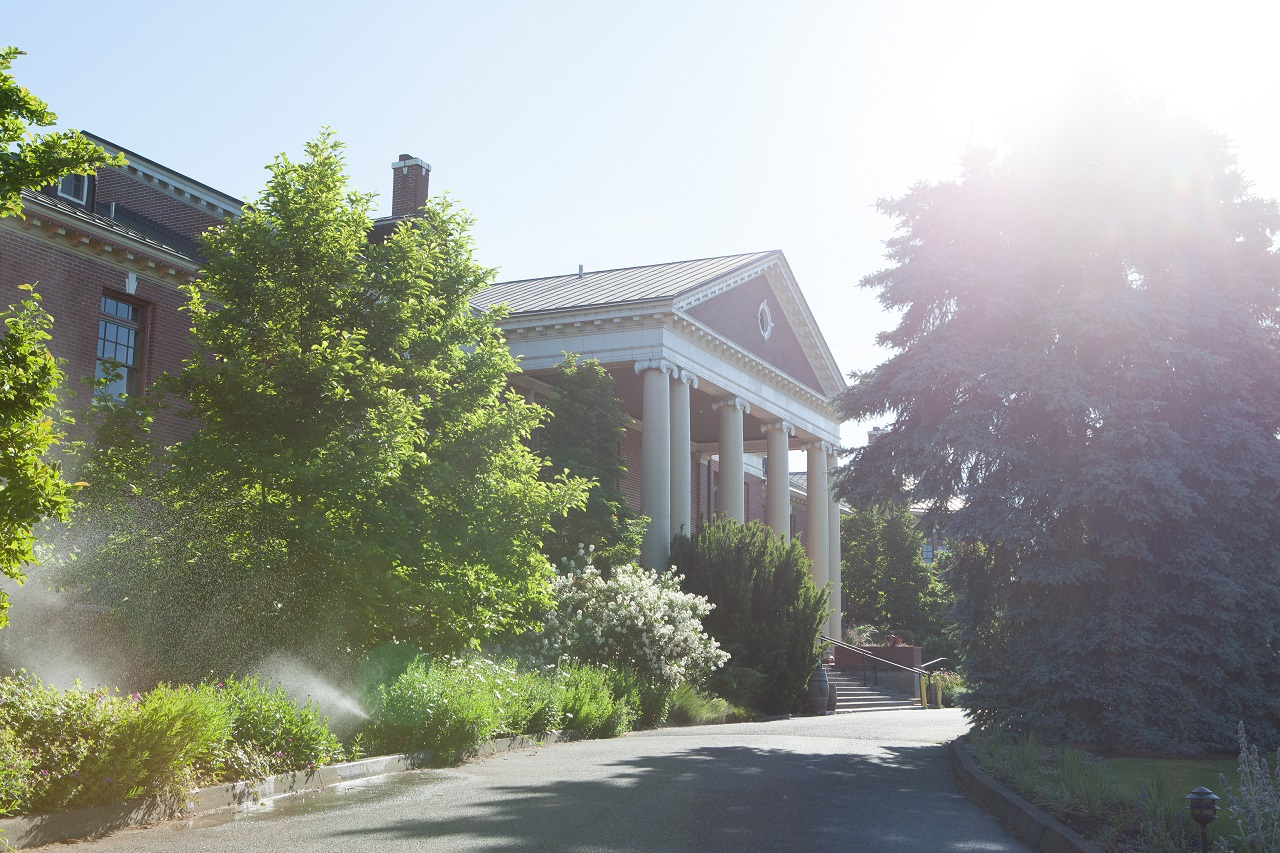 exterior of the grand lodge in forest grove with sunlight over the trees